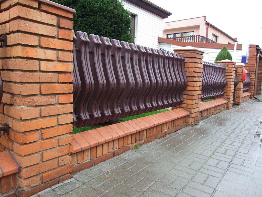 Ogrodzeniem z wykorzystaniem sztachety plastikowe oraz słupki ceglane. Obraz za https://ogrodzeniaplastikowe.pl/galeria-ogrodzen-exclusive/